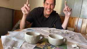 Man presenting two finished ceramic cups